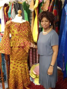 A black businesswoman shows a traditional african outfit in bright yellow and red fabric on a mannequin