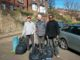 Three men doing a litter pick on Grimesthorpe Road. 3 men are looking at the camera, smiling. 2 of them have a white litter pick stick in their hands. Each of the 3 men has a black bin liner full of litter in front of them. The background image is sunny and you can see houses and parked cars.