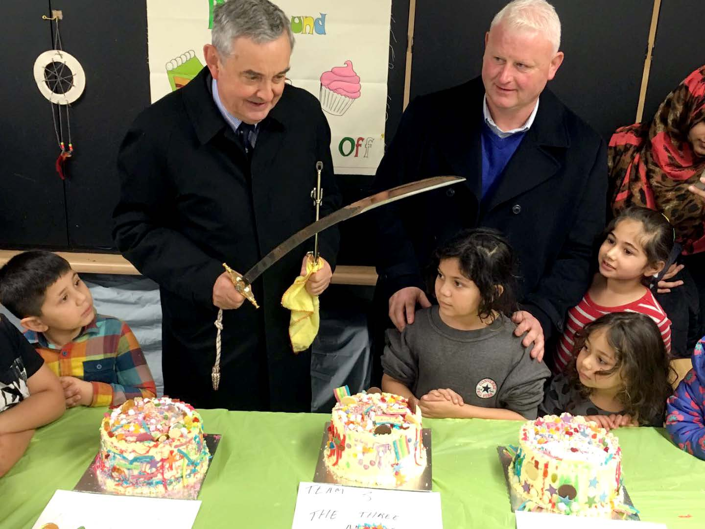 Lord Lieutenant with ceremonial sword at playground.Patrick meleady and four children in the photo with three cakes in front of them.