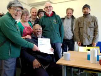 8 people , one is sitting holding a step out Sheffield leaflet.
