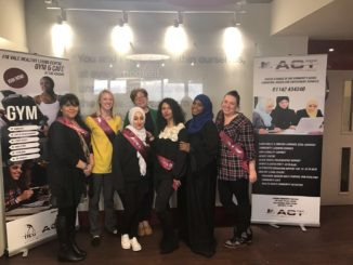Seven women at healthy Living Centre with big ACT posters.