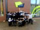 Children and teache some crouching, some standing, all with arms outstretchedr outdoors below the sign for Oasis Academy
