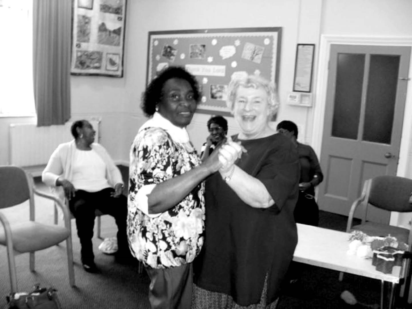 Two ladies dancing, threeo ther ladies sitting down, laughing in the background at St James friendship group