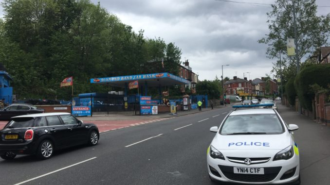 A police car parked in front of the blue cordoned off frontage of Diamond Hand Car Wash
