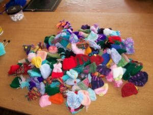 a pile of woollen hats that have been knitted; a variety of colours
