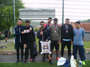 a team of eight boys they pose with their medals and trophy smiling in a football field.