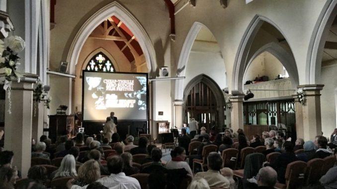 In the photo we can see the interior of the church, a lot of public sitting, enjoying the reproduction of a film, In the background we see a big screen projecting the film.