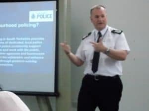 a man dressed in a police uniform standing in front of a screen