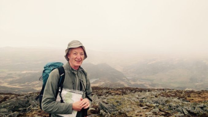 Dr McCullough standing on some rocks, with a hat, a rucksack and some paperwork in his hand. He is smiling looking at the camera.