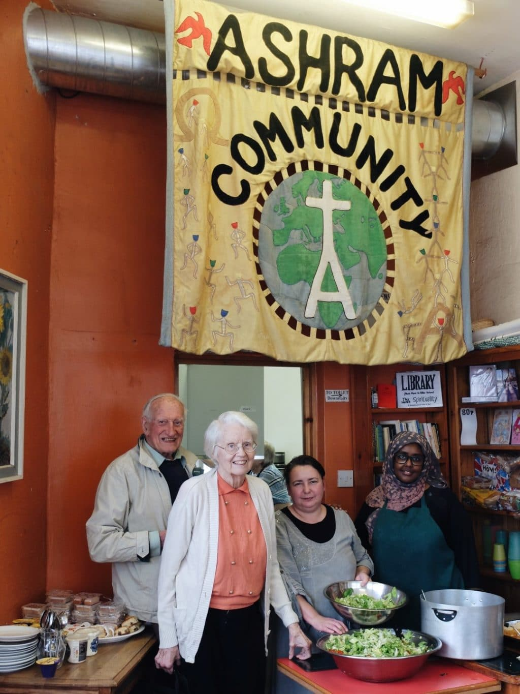 An older couple a white woman and a Muslim woman stand underneath an 'Ashram Community' banner