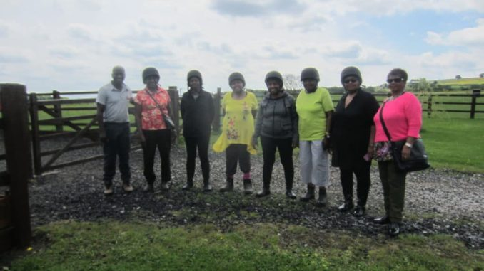 Group of eight people standing, six women and two men, six of them wearing a riding helmet over their heads.the photo is made in a field where horseback riding.