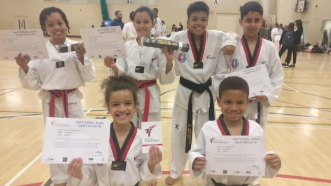 Group of six children, three girls and three children, dressed taekwondo clothes proudly showing their certificates.