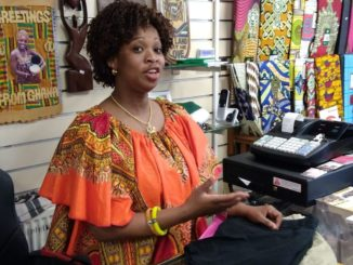 Amie Bangura dressed in a colourful african dress behind her shop counter.