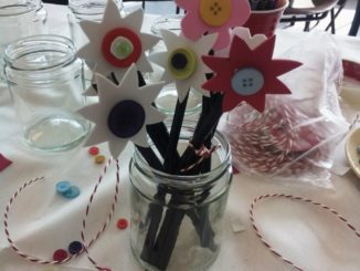 In the photo we can see a colorful bouquet of flowers, made by craft materials inside of a glass jar in a very nice decorated table.