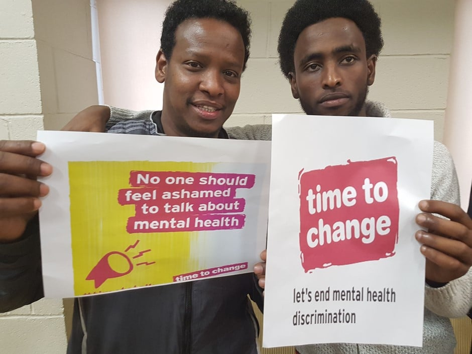2 Somalian Gentlemen standing up holding posted saying that it's time to change