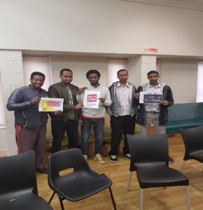 5 Somalian gentlemen stood in a room holding up posters saying that it's time to change