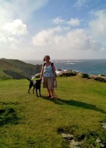 Yvonne standing on grass, on top of a cliff, with her black dog by her side. She is dressed for walking, wearing sandals and shorts and a vest top. The wind has blown her pony tail to one side. She is smiling. The sea and sky are in the background, the sun is shining.