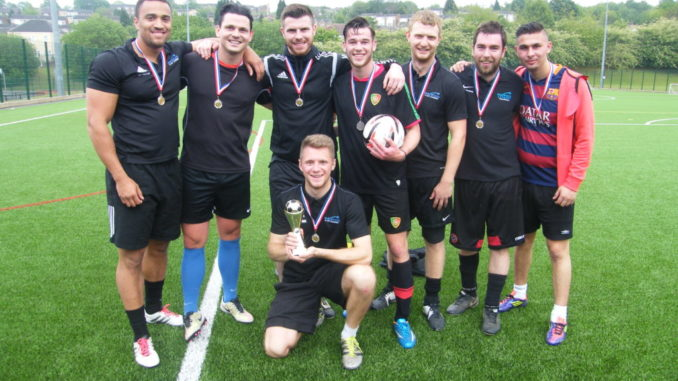 In this photo there are eight men who belong to a football team called Parkwood Academy. They are winners. One is kneeling down holding a trophy, another is holding a ball. They all look happy and are all smilimg with a sense of achievement. They look like they are on the football pitch they have played on.