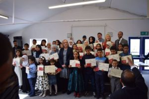 Group of about twenty-five people, mostly boys and girls with their corresponding certificates with local politicians representatives and some teachers.
