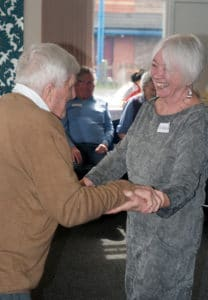 A lady with grey hair and a grey dress is smiling, whilst dancing with a man with grey hair facing her.