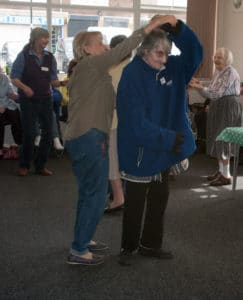 2 ladies dancing, holding hands, one is twirling round underneath the arm of another. they are wearing casual clothes, and they are dancing inside a room.