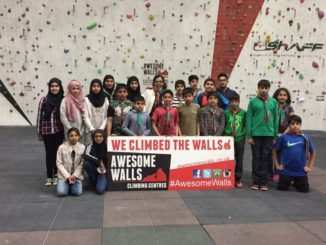 20 young people and young children posing for a photograph in front of a poster advertising Awesome Walls