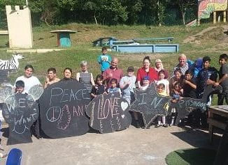12 children from different ethnic backgrounds aged 2-13 stand in a playpark with play leaders in front of signs they have made on chalkboards saying 'peace and love'