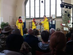 Audience backwards and three actors wearing a bright yellow dress on stage performing. With a big window in the background.