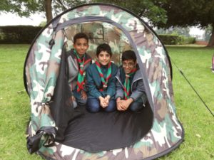 3 boys in Scout uniform in a tent.