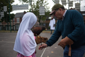 A gentleman helping a young girl wearing a pink dress and white head scarf hold a bird of prey on her outstretched left arm