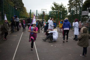 Children and adults in the playground. Some adults stood, one man on floor. Young girl in pink fancy dress carrying a toy walking towards camera