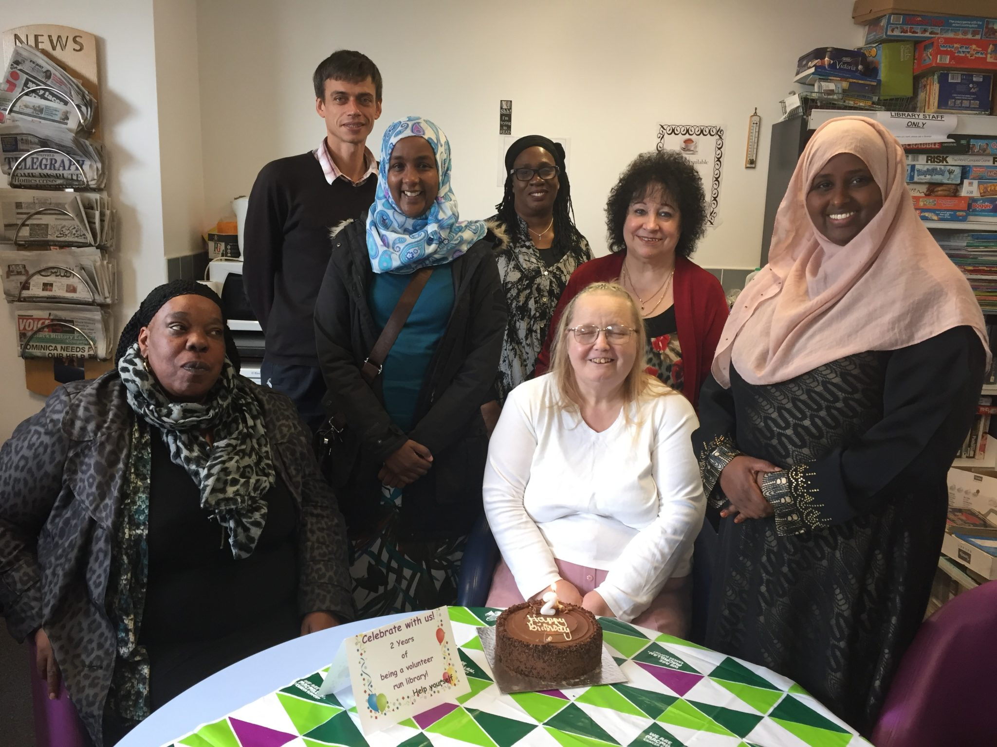 6 women and one gentleman all smiling at the camera. two of the women are sat down at the front and the rest stood behind them. There is a table at the fron with a birthday cake on it.