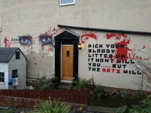 "Wall on outside of house with message, ""Pick your bloody litter up, it won't kill you.....but the RATS will."""