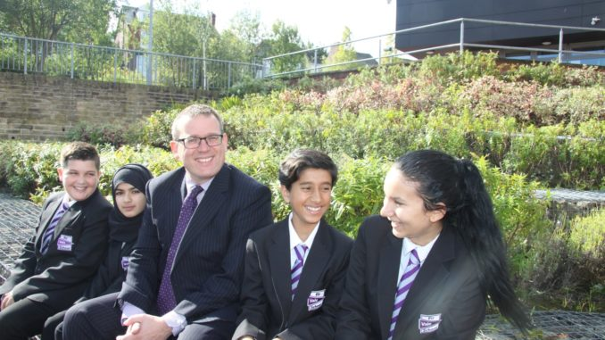 Mr Hawkins sat in the middle of four Fir Vale Academy Students with green and purple foliage in the background