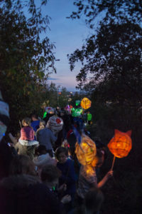 A parade of adults and children walking away from the camera carrying illumines orange, green and bright lanterns against an evening dark blue sky