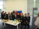 Agroup of 8 students and 2 teahcers all stood looking at camera behind a table full of refreshments