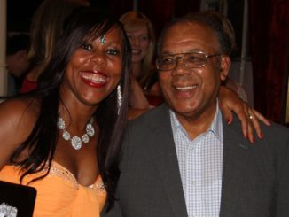 A woman stands and smiles at the camera with her arm around an older man to her left
