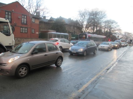Two lines of cars sit in traffic on a wet Barnsley Road.