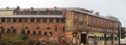 An old building, derelict in parts, with a row of shops to the right hand side.