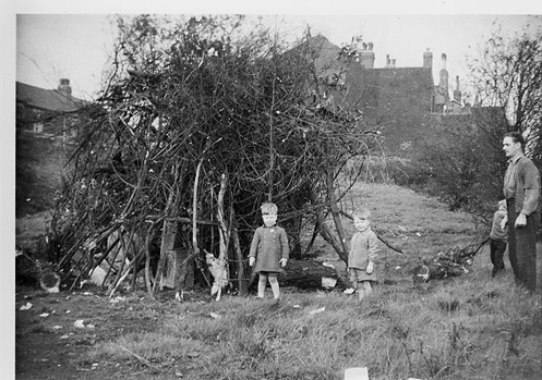 An old black and white phootograph of two young children standing in front of a loosely packed, unlit, bonfire. On the right hand side of the photo a man stands watching the children, with another child by his side, holding onto his arm.