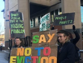 Two protestors hold up a sign reading 'Say No To Eviction' outside the magistrates court. More protestors are holding banners behind them.