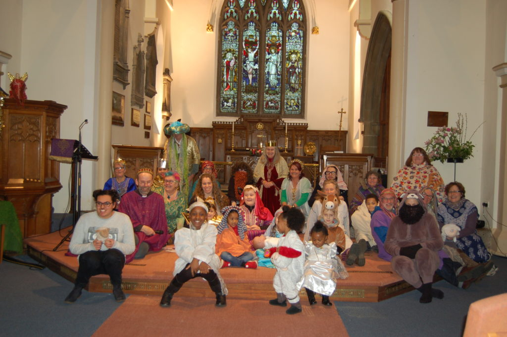 Performers at the Christ Church Nativity sit together on stage.
