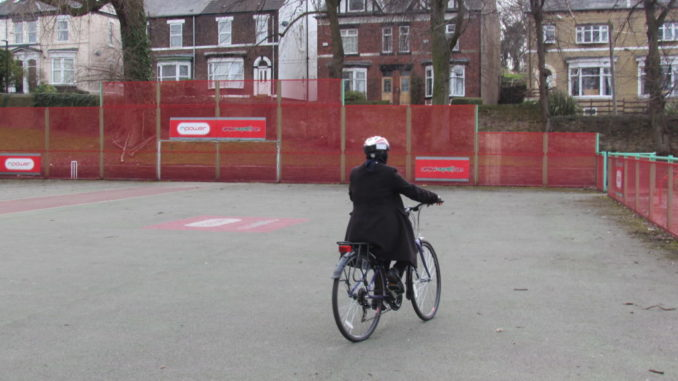 Woman on cycle facing away from camera