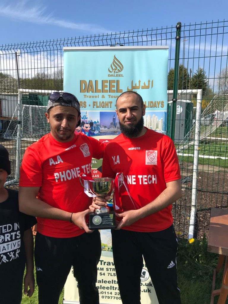 2 Men holding trophy
