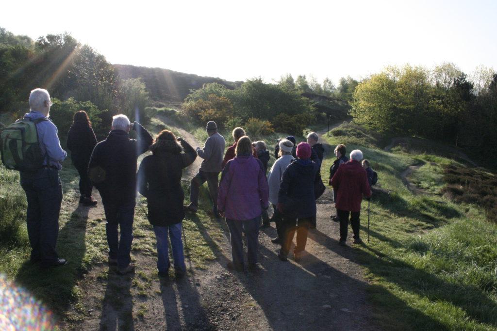 Over twenty people listen to birds on Parkwood Springs