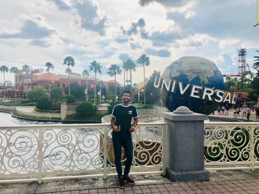 Adnan Hussain posing on bridge in front of Universal Globe