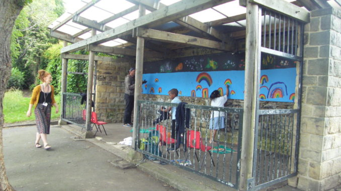 Children paint rainbows on the Abbeyfield Park shelter mural.