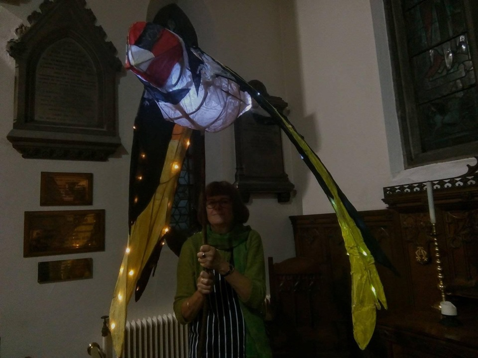 Goldfinch lantern held high.