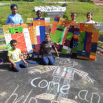 "Kids chalk on the ground ""come and help paint."""
