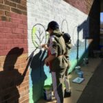 Children painting mural during Healthy Holidays week